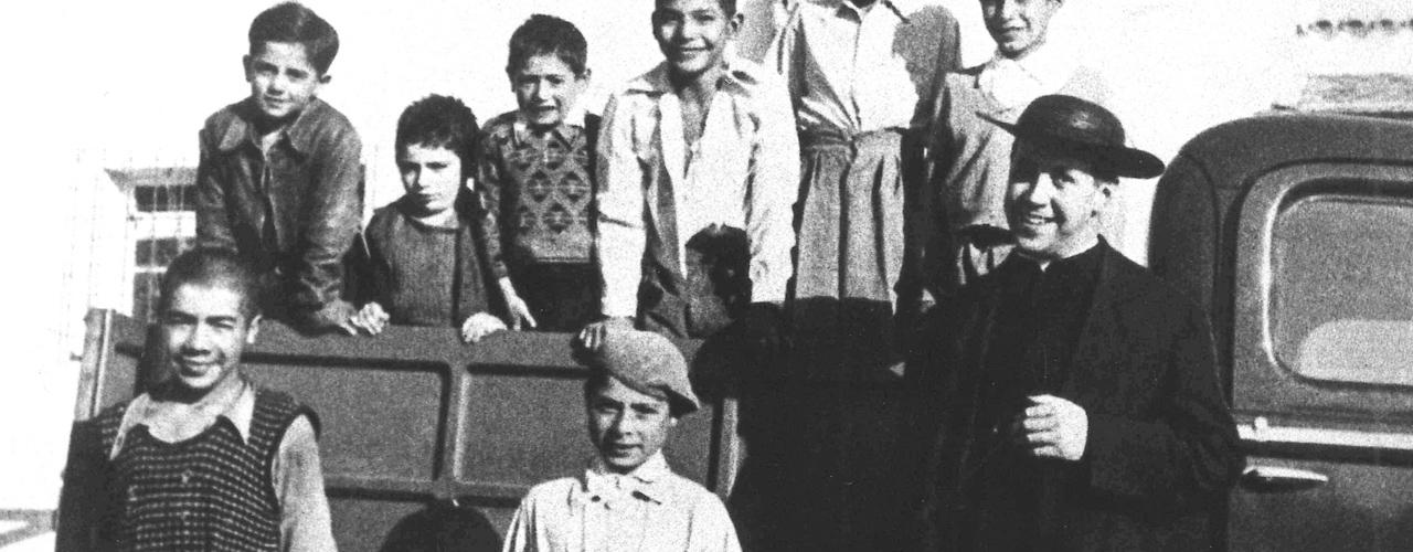 Foto de alberto Hurtado, con su camioneta y unos niños